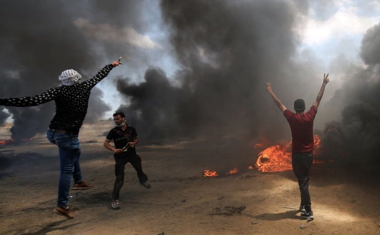 Manifestanţi palestinieni folosesc praştii cu pietre în timpul ciocnirilor cu forţele de securitate de-a lungul frontierei dintre Fâşia Gaza şi Israel, 14 mai 2018.