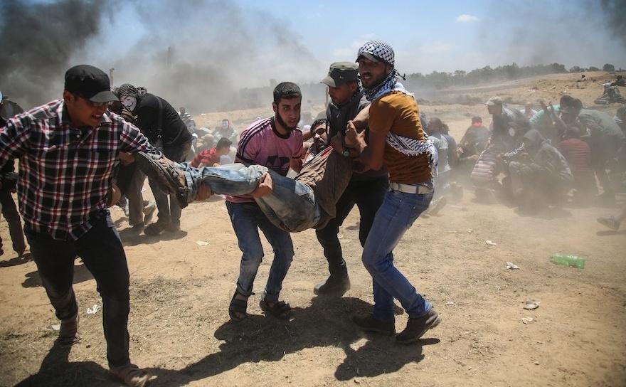 Manifestanţi palestinieni transportă un bărbat rănit în timpul unui protest împotriva mutării ambasadei americane în Ierusalim. Scena a fost surprinsă în apropierea taberei de refugiaţi Al Bureij, lânga graniţa dintre Gaza şi Israel, 14 mai 2018.