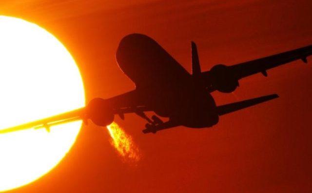 Un avion decolează sub Soarele care apune.