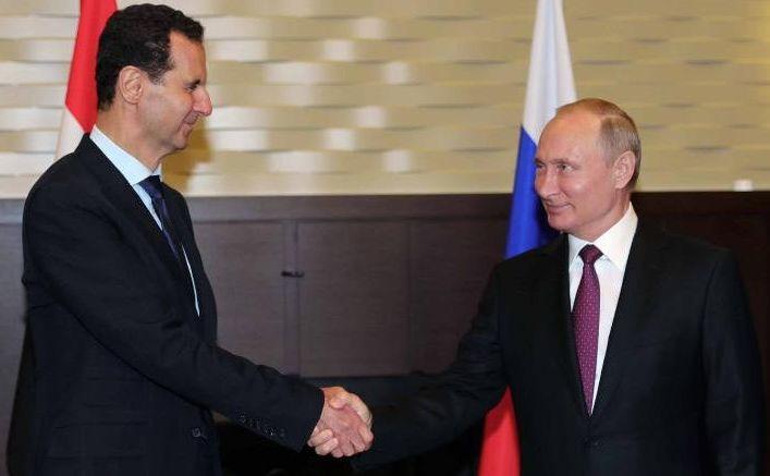 Preşedintele rus Vladimir Putin (dr) dă mâna cu omologul său sirian Bashar al-Assad în timpul întâlnirii lor din Soci, Rusia, în 17 mai 2018.