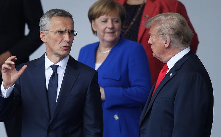 Preşedintele american Donald Trump (dr), cancelarul german Angela Merkel (centru, fundal) şi secretarul general al NATO, Jens Stoltenberg (st) participă la ceremonia de deschidere a Summitului NATO din 2018, în Bruxelles.
