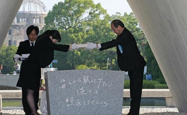 Un reprezentant al familiilor victimelor tragicului accident înmânează primarului oraşului Hiroshima, Kazumi Matsu, o carte cu numele victimelor