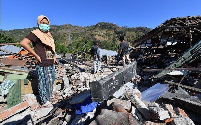 Oameni caută printre ruinele caselor lor distruse de un cutremur în Menggala, la nord de insula indoneziană Lombok, 8 august 2018.