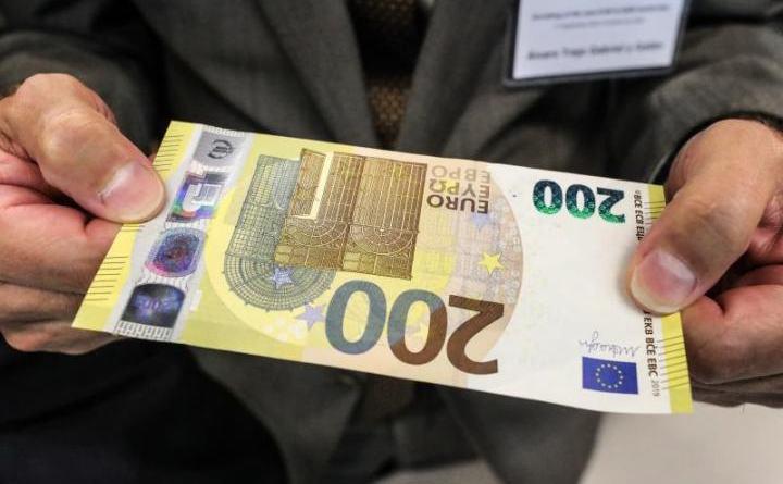Un bărbat ţine în mână o bancnotă de 200 de euro în timpul dezvăluirii noilor bancnote de 100 şi 200 euro la sediul BCE în Frankfurt, 17 septembrie 2018.