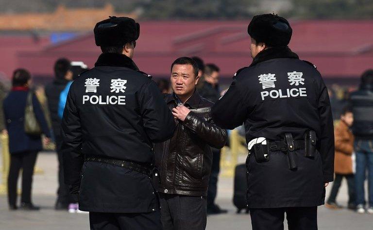 Poliţişti chinezi interoghează un bărbat în Piaţa Tiananmen din Beijing, China, 2 martie 2015