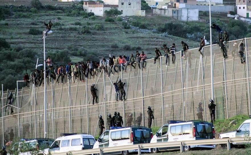Imigranţi africani traversează gardul de frontieră între Maroc şi enclava spaniolă Melilla, octombrie 2014