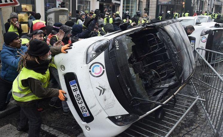 """Manifestanţi """"Vestele Galbene"""" distrug automobile în timpul unui protest desfăşurat în 1 decembrie 2018, în Paris, împotriva creşterii preţurilor la carburanţi şi a costurilor de trai"""