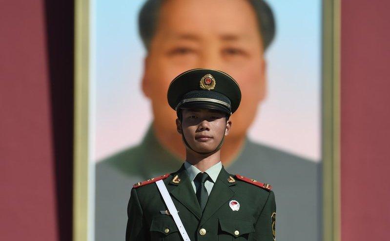 Un membru al poliţiei paramilitare stă de pază în Piaţa Tiananmen din Beijing, China