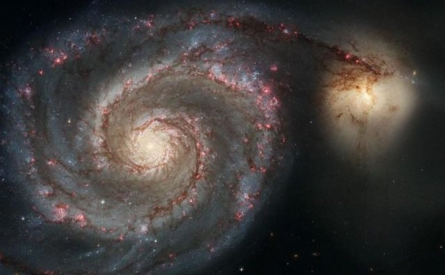 Galaxia Whirlpool (M51a) şi galaxia însoţitoare (M51b). Telescopul spaţial Hubble prezintă o contopire a două galaxii, care seamănă destul de bine cu Calea Lactee şi cu Marele Nor al lui Magelan.