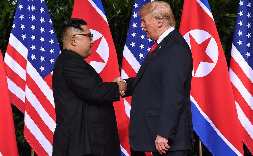 Preşedintele american Donald Trump (dr) dă mâna cu dictatorul nord-coreean Kim Jong-un la începerea summitului lor din Singapore, 12 iunie 2018