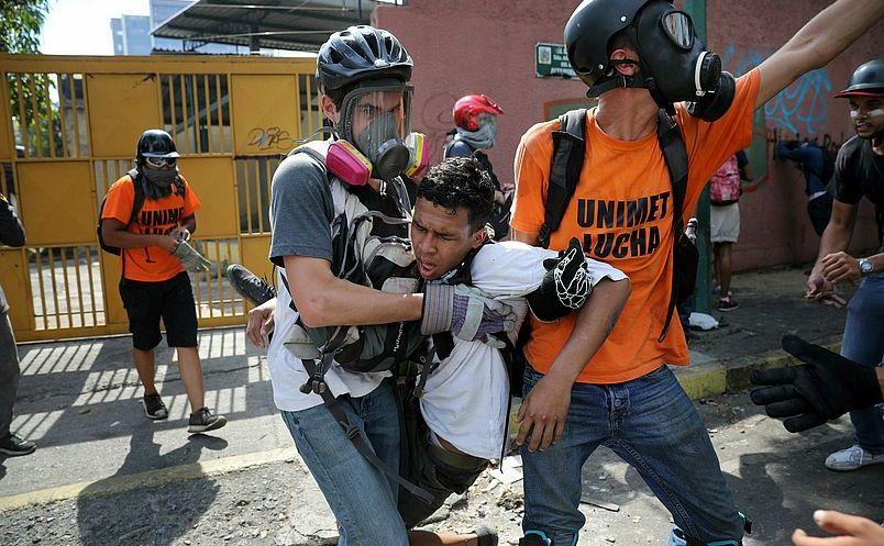 Un manifestant anti-guvern este transportat de alti manifestanţi după ce a fost afectat de gazele lacrimogene folosite de forţele de securitate loiale regimului Maduro în Caracas, 1 mai 2019