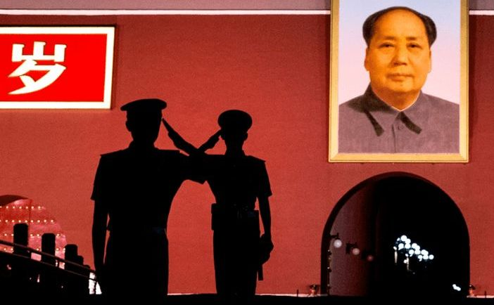 Ofiţeri poliţiei paramalitare chineze se salută în faţa unui tablou al dictatorului Mao Zedong în Piaţa Tiananmen din Beijing,  China