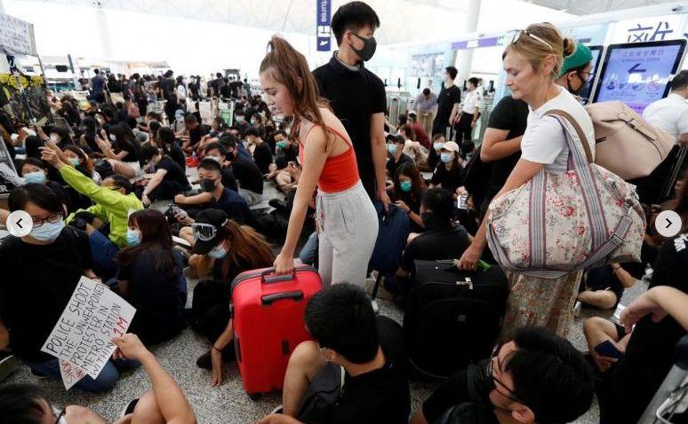 Pasagerii ȋşi fac loc printre manifestanţi ȋn timpul unui protest la aeroportul din Hong Kong, 13 august 2019
