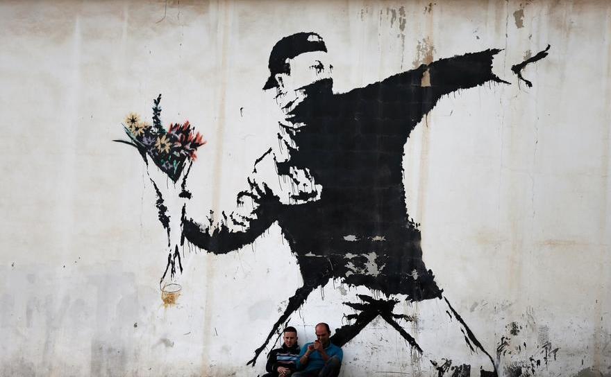 Graffiti realizat de renumit al artistului britanic Banksy pe zidul unei benzinării din oraşul Betleem, Cisiordania
