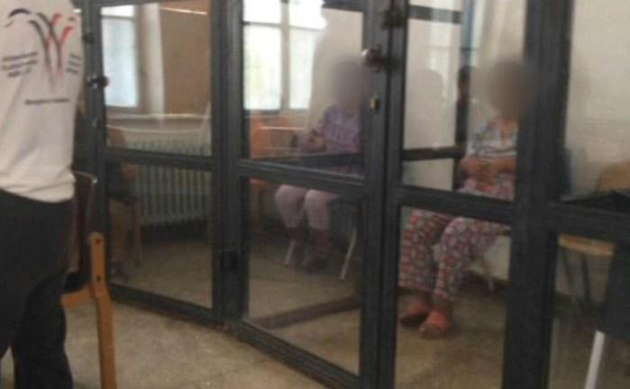 Persoane cu dizabilităţi psihosociale şi intelectuale, închise în cuşti deaproximativ 2,5 m înălţime, cu ramă metalică şi plexiglas transparent