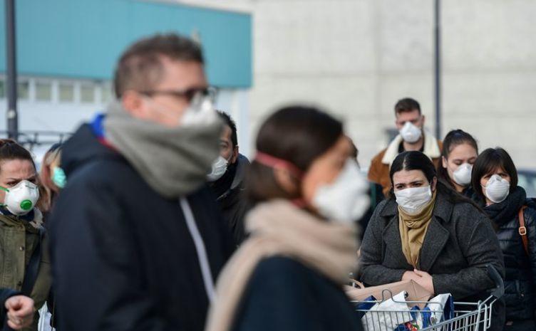 Rezidenţi ai oraşului italian Casalpusterlengo poartă măşti de protecţie în timp ce merg la un supermarket, 23 februarie 2020