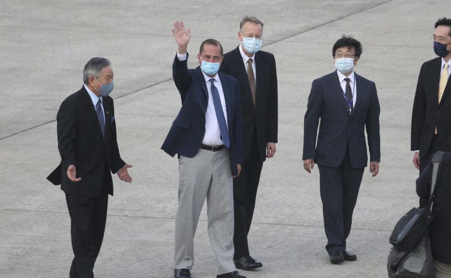 Secretarul pentru sănătate Alex Azar, al doilea din stânga, face cu mâna către presă pe aeroportul Songshan din Taipei, Taiwan,  9 august 2020.