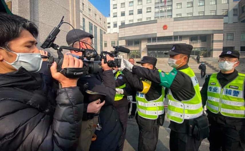 Miliţia chineză încearcă să oprească jurnaliştii în faţa tribunalului unde se judecă procesul lui Zhang Zhan, în oraşul Shanghai