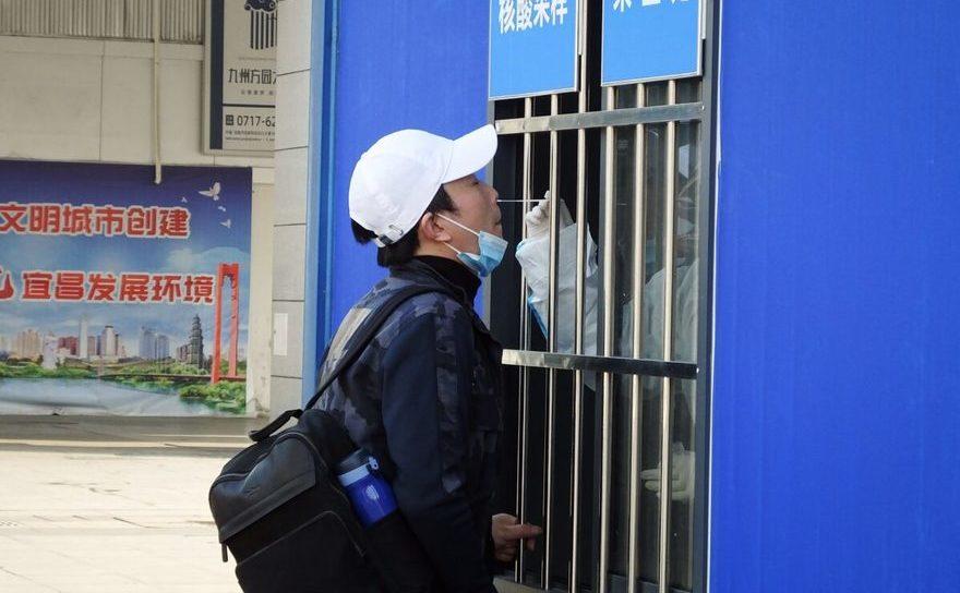 Un chinez oferă probe ale mucoasei nasale pentru teste COVID-19 lângă gara din Yichang, provincia Hubei - 28 ianuarie 2021