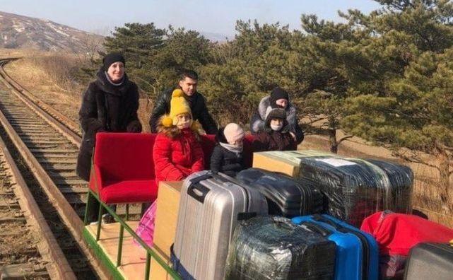 Diplomaţi ruşi părăsind Coreea de Nord împingând o drezină