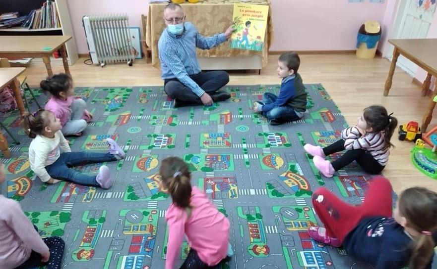 Bogdan Davidescu citind poveşti copiilor de la grădiniţa satului Vistieru, comuna prahoveană Şotrile