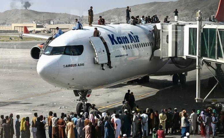 Cetăţeni afgani se caţără pe un avion de călători pe aeroportul din Kabul, Afganistan, 16 august 2021