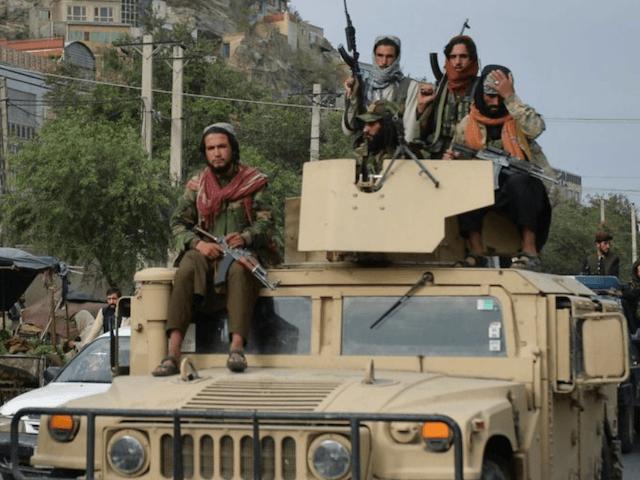 Talibani urcaţi pe vehiculele auto blindate ale armatei americane,  capturate după preluarea controlului asupra armatei afgane, Kabul, 31  august 2021